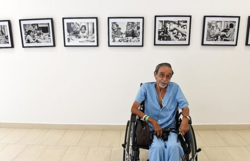 Alan Lee sits in his wheelchair in front of photos of hospice life