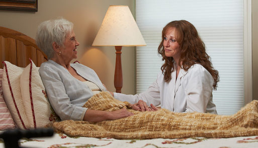 Elderly woman and nurse holding eachother's hands in a hospice center