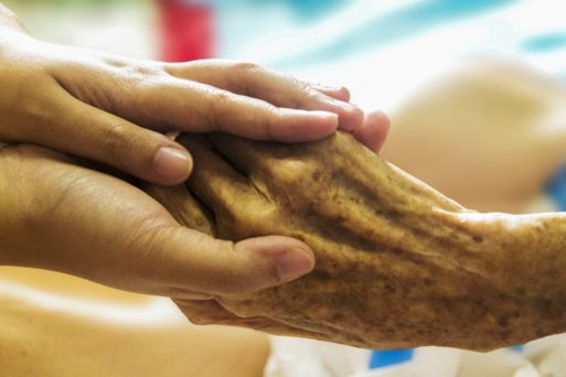 Elderly person's hand clutching a young person's hand symbolizing a life review.