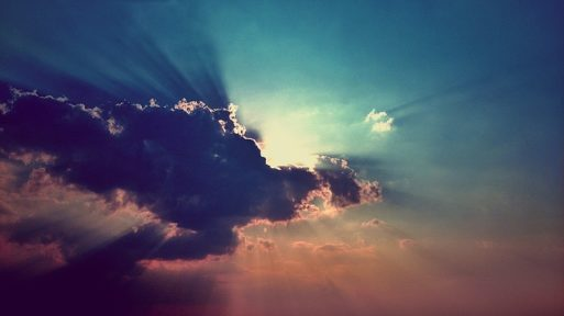 Sky and sun's rays darkened by a black cloud