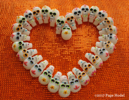 Heart made of Halloween candy with skulls on an orange brackground