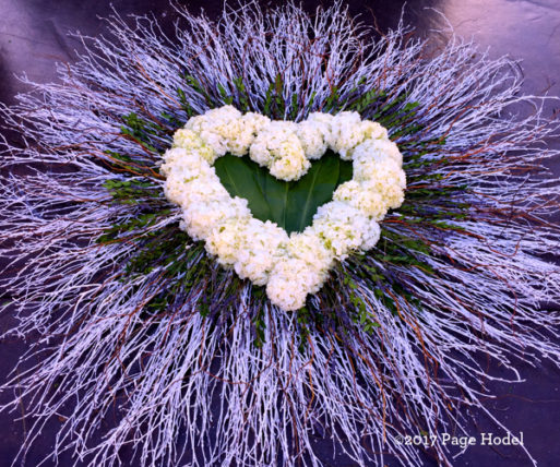 Purple dried flowers around a white handmade heart