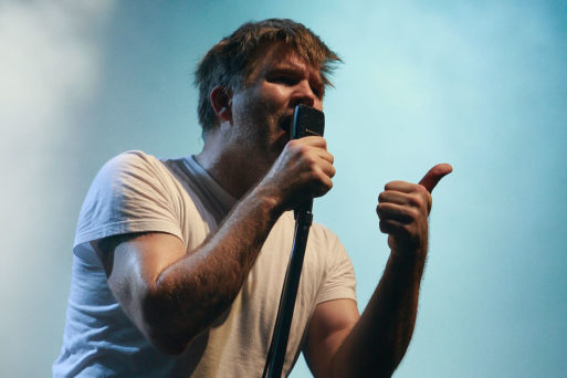 "James Murphy of electronic group LCD Soundsytem singing ""Something Great"" into a microphone"