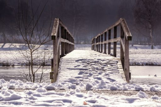 Wooden foot bridge covered in snow symbolizing the transition from life to death