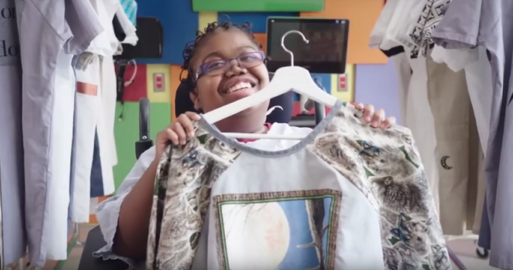 A young girl holds up her new hospital gown redesign, which features an illustration of a bird and other intricate details