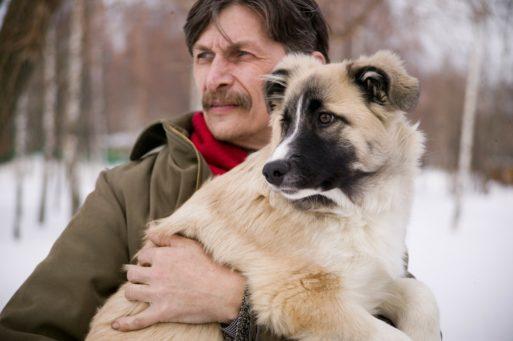Man holding a dog symbolizing comfort