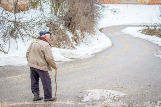 Elderly man walking down a windy road with a walking stick.