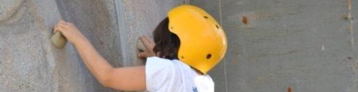 A child climbs a rock wall at Kids Camp