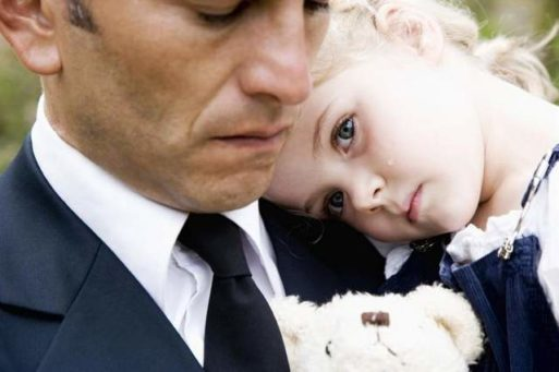 A little girl in her father's arms at a funeral