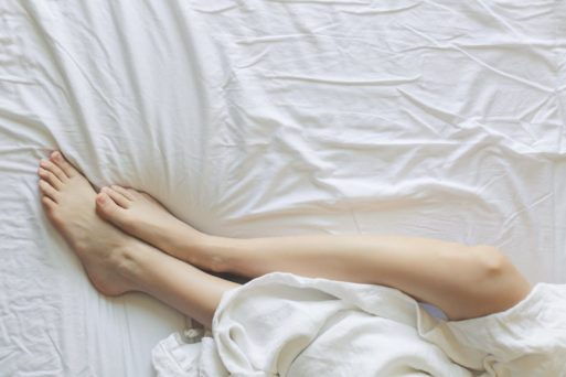 A photo of a person lying in bed, with their legs sticking out from a white sheet