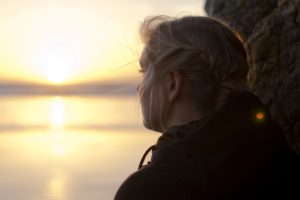 Girl looking out onto the ocean as the sun is setting symbolizing grief