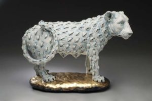 A sculpture about loss, featuring a grey lion that is covered in small eyeballs