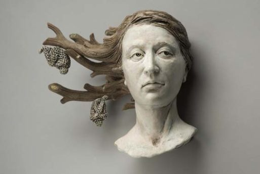 A sculpture about loss, featuring a woman's head, whose hair is being transformed into tree branches with two honeycombs hanging from the tips of the branches