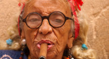 An elderly woman wearing glasses smoking a cigar.