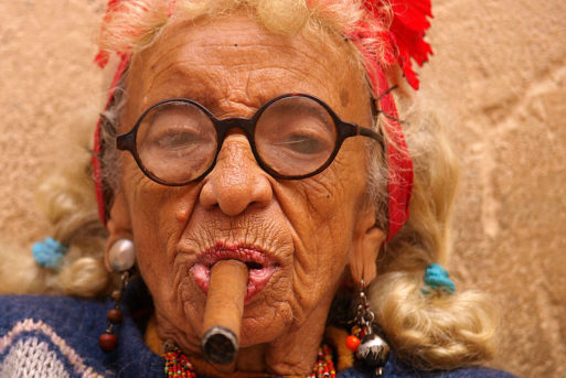 An elderly woman wearing glasses smoking a cigar