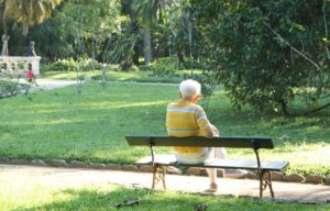 Elderly man sitting alone on park bench symbolizing aging and loneliness.