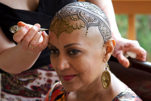 Woman with cancer getting a henna tattoo
