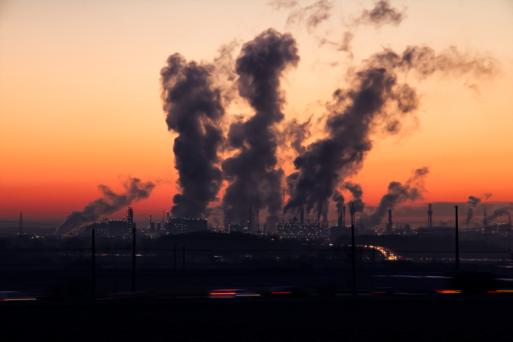 Factory smoke stacks emitting smoke at dusk