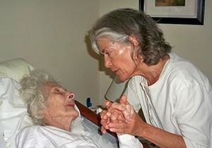 Irene Smith holds a patient's hand in a hospice facility showing the value of touch