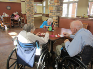 A group of elderly people sit at a table in a nursing home eating dinner