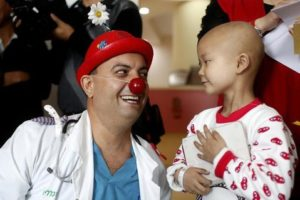 A clown doctor smiles at a young child who is staying at a hospital