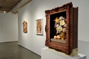 A photo of the still life vanitas gallery show, featuring a wooden frame with real sculpted objects inside of it, like a full flower bouquet