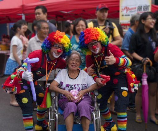 An elderly woman in a wheelchair poses with two people dressed up as clowns and clown doctors