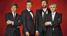 Portrait of Britsh band Duran Duran wearing suits.
