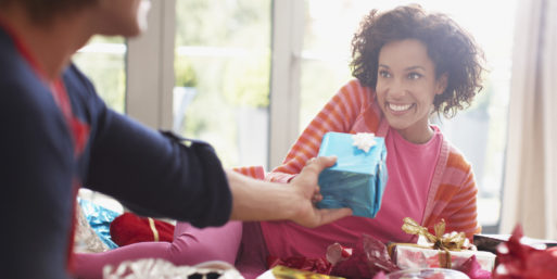 Man giving a gift to a woman for Christmas