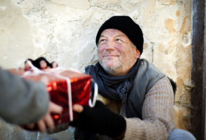A person giving a Christmas present to a homeless man
