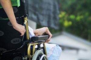An elderly woman sits in a wheelchair, which is being pushed by a nursing home staff member