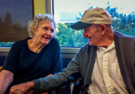 Gloria Single sits next to her husband, Bill Single in a nursing home; AARP Foundation is suing the home for illegal nursing home evictions