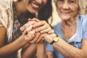 Elderly woman and young woman smiling and clenching hands together symbolizing palliative care