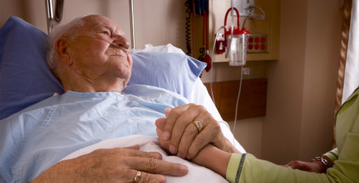 Elderly man in hospital bed holding someone else's hand representing palliative care