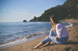Woman sitting on a beach looking at the sand symbolizing grief