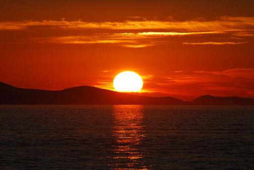 """A bright orange sunset, similar to the one described in the song """"The Sun is Burning"""""""