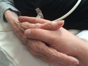 A son holds his elderly mother's hand; the last wishes of the dying often include spending time with loved ones