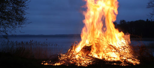 A brightly burning fire by the side of a lake in the dark