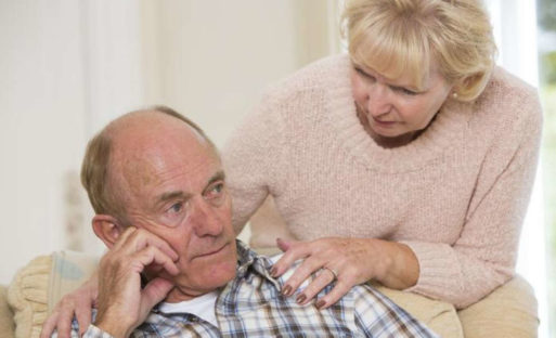 Elderly man sitting on couch while wife consoles him symbolizing mild cognitive impairment