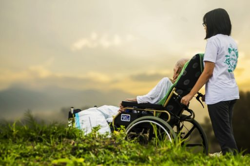 An elderly person is pushed in a wheelchair in a field of grass by a nurse, as she helps fulfill the last wishes of the dying