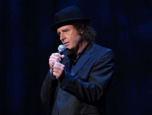 Comedian Steven Wright performing stand up with a microphone while wearing a dark suit and hat.