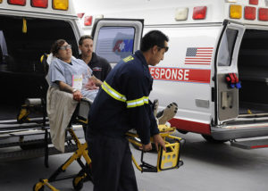 Two paramedics carry a woman who might be a candidate for cryopreservation on a stretcher out of an ambulance