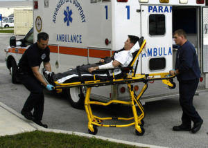 Two paramedics carry a man on a stretcher toward an ambulance in emergency medical situations