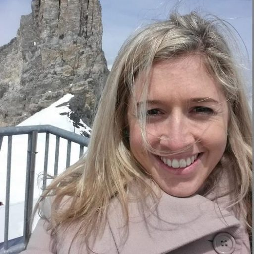"""Selfie photo of Holly Butcher who wrote """"a note before I die"""", wearing a coat standing in front of a rocky pillar with snow on the ground"""