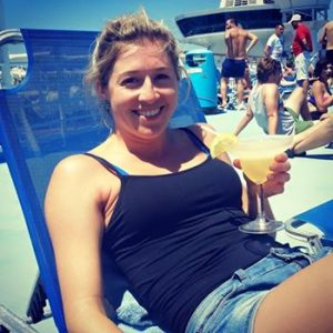 """Photo of Holly Butcher drinking a cocktail sitting in a blue beach chair long before she wrote a """"note before I die"""""""
