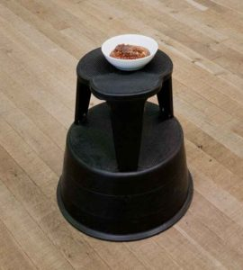 """Photo of a footstool with a bownl of honeycomb placed on top, part of Damien Hirst's art installation """"Pharmacy"""""""
