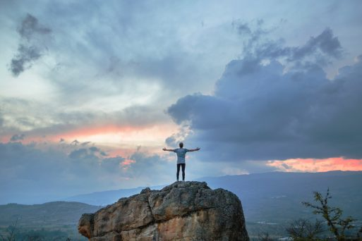 Man standing with arms wide open on a peak looking at sky